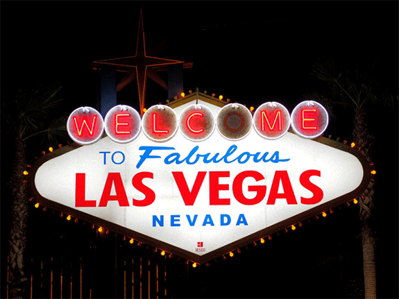 The classic sign reading 'Welcome to Fabulous Las Vegas Nevada's sign is seen at night brightly lit up with the 'O' in 'Welcome' burned out.