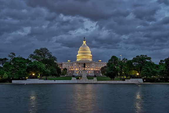 The U.S. Capitol Building is seen lit up during early evening as grew clouds swirl above. The frame is set back to show the reflecting pool at the bottom half of the image with bright and dark green trees blending the transition into the sky. The Capitol dome is bathed in golden yellow.