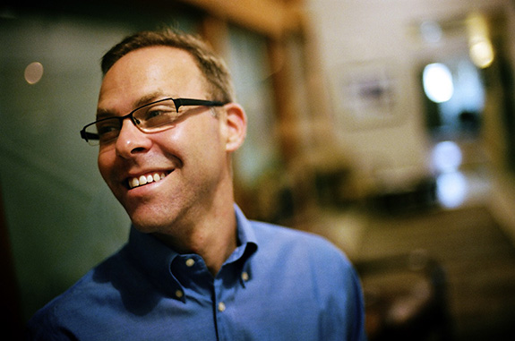 A portrait of a smiling Kris Krane is seen with him wearing a blue shirt and glasses shot against a blurry background.