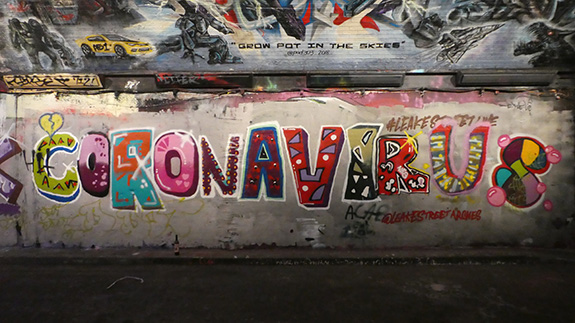 A large bright piece of graffiti covers a gritty concrete wall with the word 'CORONAVIRUS'.