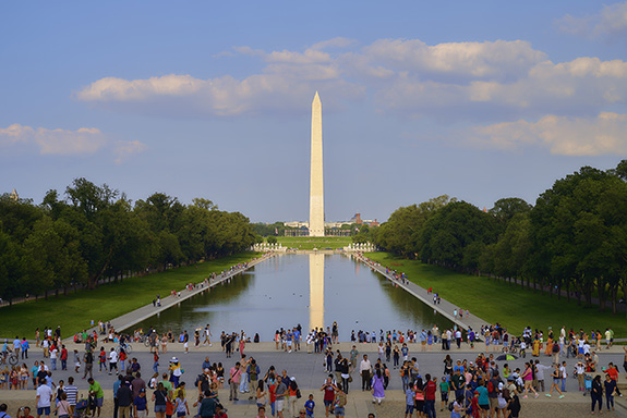 The Washington Monument fills the frame's center flanked on either side by a green lawn bordered by twin stretches of trees thick and green. Crowds of tourists surround the reflecting pool.