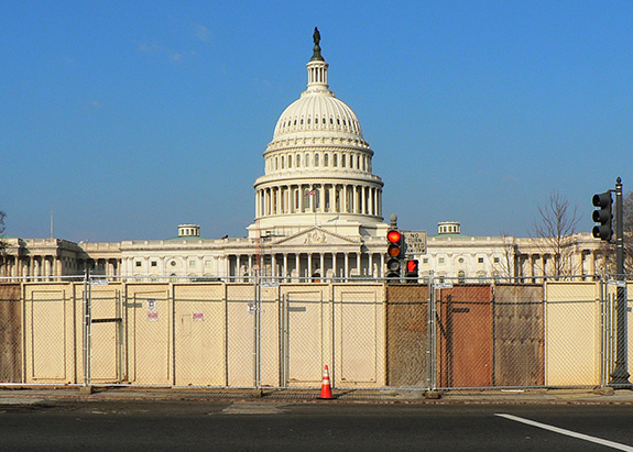 The U.S. Capitol building is seen in bright daylight under a blue cloudless sky hidden behind a barrier of both chainlink and paneled fencing.