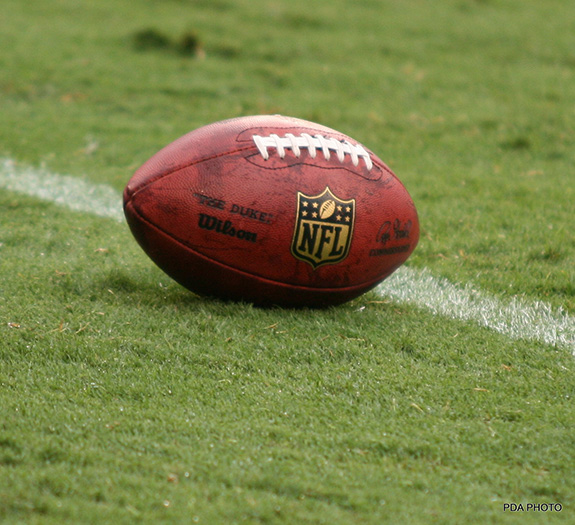 A close up photo shows a well-used leather football emblazoned with the NFL logo on it sitting laces up on an equally used green grassy field- sitting just shy of a white painted line marker.