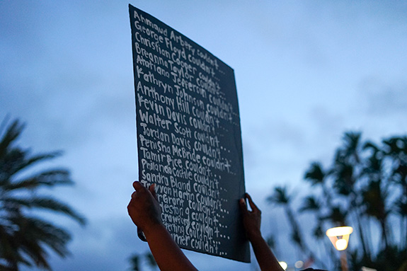 A hand-hand sign is held aloft during a protest reading the names of black people recently killed by police. 20 names are listed with each followed by the word 'couldn't'.