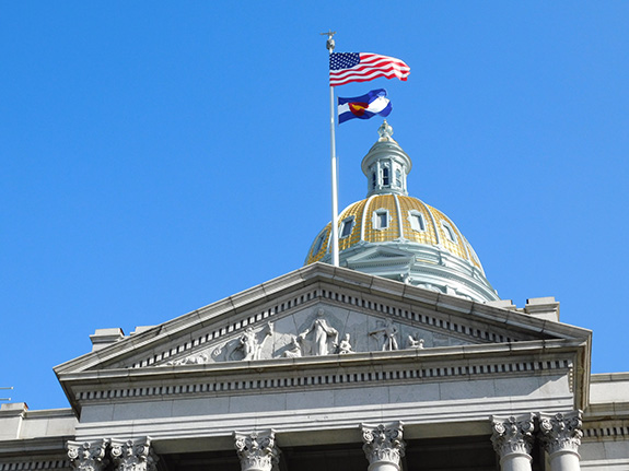 The golden-domed capitol building of Colorado is seen from ground-level looking up with the building- fronted by a flagpole with both the U.S. and state flags - set against a cloud-less blue sky.