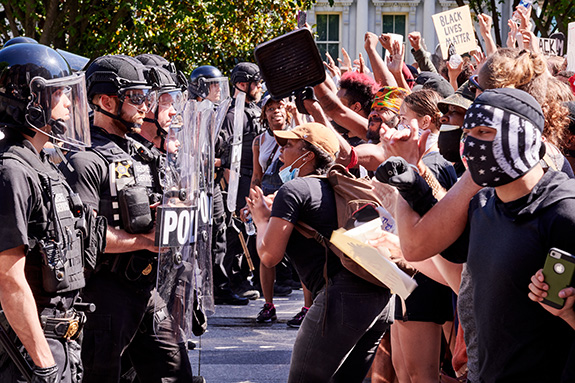 A large group of protestors faces off against a line of black suited riot police during a sunny day during a protest against the police murder of George Floyd and general systemic racism and oppression.