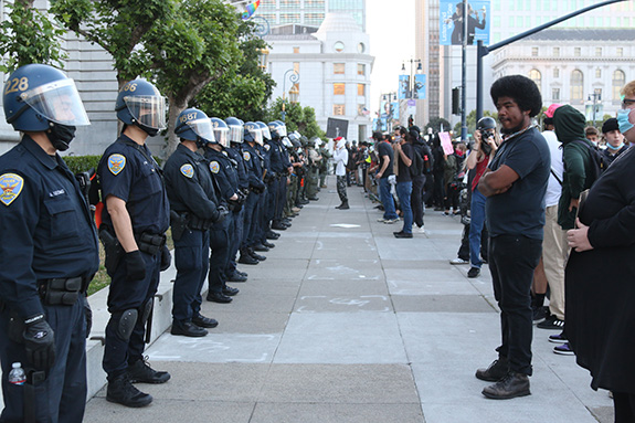 A young black man protesting stands across from a line of faceless police officers hiding behind helmets and face shields on a clear city sidewalk.