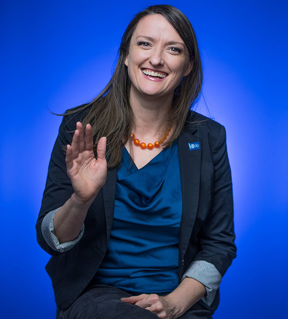 A well-lit portrait of Betty Aldworth shows her set against a blue background while smiling and and waving hello to the camera.