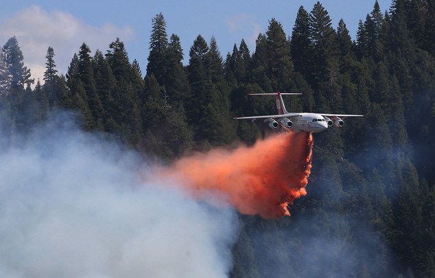 A firefighting airplane releases its rusty-red load of fire retardant chemicals on an unseen fire below. The smoke is reaching up towards the plane which is set against a backdrop of tall green pine trees fringing a light blue-sky with just the barest hint of a cloud.