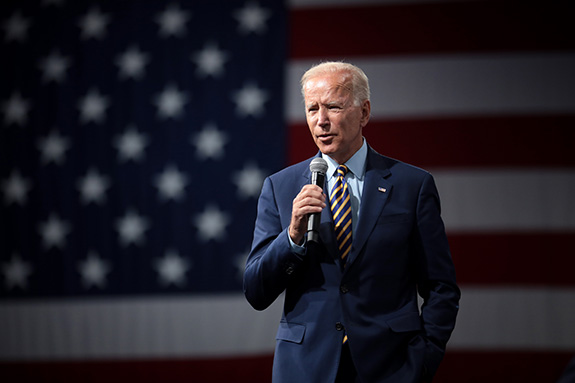 Democratic presidential candidate Joe Biden stands on stage holding a microphone speaking in front of muted-toned American flag. Biden is wearing a blue suit and is squinting with both the bright light and an earnest fire.