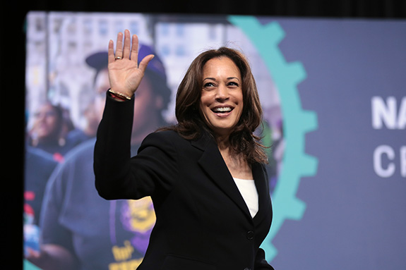 Presumed Democratic Vice Presidential nominee Kamala Harris waves off camera as she appears to walk on stage to speak in front of a screen. She is smiling broadly.