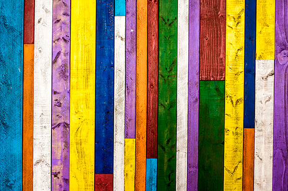 A series of wooden boards- each painted a different bright color- is stacked up side by side running vertically across the frame. Some boards are shorter than others, so some columns feature boards of two colors. Eight colors in all are used- with repeats.