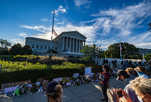 The U.S. Supreme Court is seen backed by a bright sun and a blue sky with wisps of white clouds. The flag flies at half mast to honor Justice Ruth Bader Ginsburg. A group of people sits to pay tribute amongst a large collection of signs and flowers left behind by mourners and well-wishers. The masks that people wear help mark the day. It