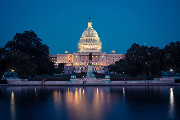 The U.S. Capitol building is seen just after sunset when the sky is all blue with not a touch of warm light to be seen. The view is from the side of the Capitol with a statue and reflection pool which shows a soft blurred image of the world above it. A handfull of people can be seen in small detail showing the scale of the full image.