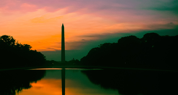 The Washington Monument is seen in dark silhouette against a muted sunset sky. The clouds frame the sunrise colors and perfectly fringe the treeline with both mirrored- along with the Monument- by the reflection pool at the base.