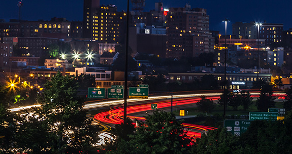 A busy shot shows a compressed view of Portland, Maine at night- with a trail of car lights below the city