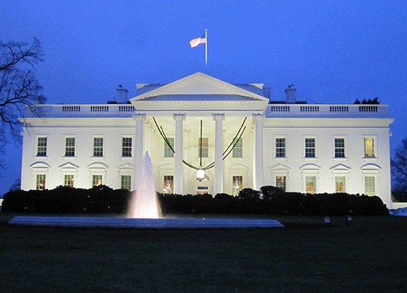 The White House in Washington, DC is seen close up- with the front of the building- lit during either early dawn or late dusk- filling the frame. The water fountain in front has a plume of conical water shooting up and a rippling American flag waves from a pole in the center of the building. the sky behind is a light purple blue.
