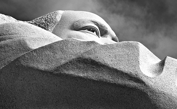 The Martin Luther King, Jr, Memorial is seen from a low angle such that you just see the eye and brow of the late Dr. Martin Luther King, Jr. looking up to the right of frame. The photo is devoid of color and the sky that can be seen is partially cloudy.
