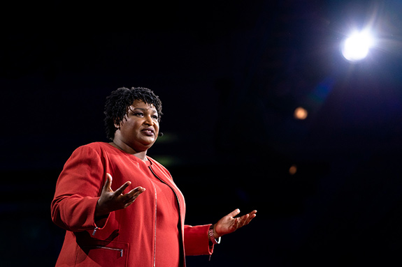 National hero Stacey Abrams speaks on stage during the 2018 TEDWomen conference. She is wearing a red dress and jacket and gesturing with both hands held wide while speaking under a bright light seen in the upper right of frame.