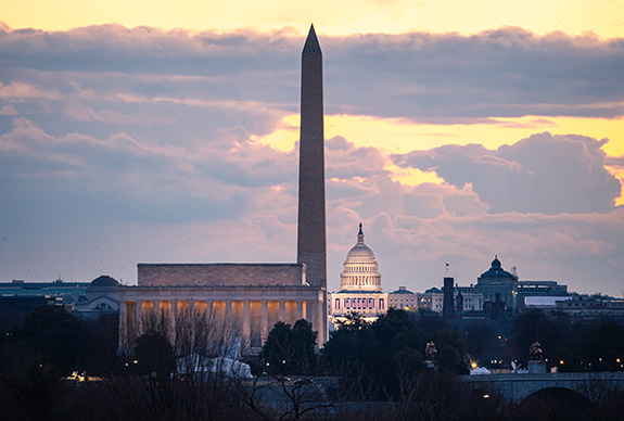 The U.S. Capitol Building is seen in the middle of the frame- small- with the Washington Monument rising up above it and setting the proper scale. The Lincoln Memorial building is seen in front of the base of the Monument and shows the compression in-frame created by the use of a long camera lens. The overall tone of the photo is rather muted, but the Capitol building is brightly lit up with a partially-cloud golden sky behind it. The image feels like there is hope in the darkness.