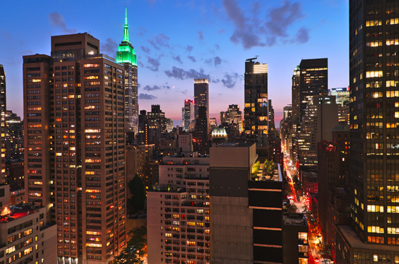 New York City is seen from a high vantage point in a building. The Empire State Building is off to the left and lit up brightly with green light. The sky is giving over to dusk and the slivered moon is small above the horizon. The one visible city street is streaked with white and red time-lapsed car lights.