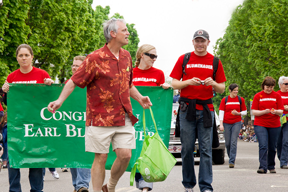Oregon congressman Earl Blumenauer walks in a parade in front of supporters carrying a green sign with his name on it. His supporters wear a red t-shirt with his last name printed with white while the congressman is wearing khaki shorts and a red and orange Hawaiian shirt.